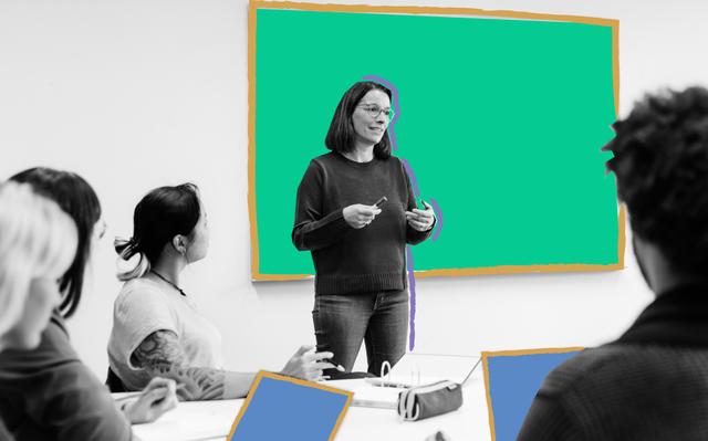 mulher em pé em frente a lousa fala para alunos, que aparecem de costas e de lado sentados em mesa compartilhada