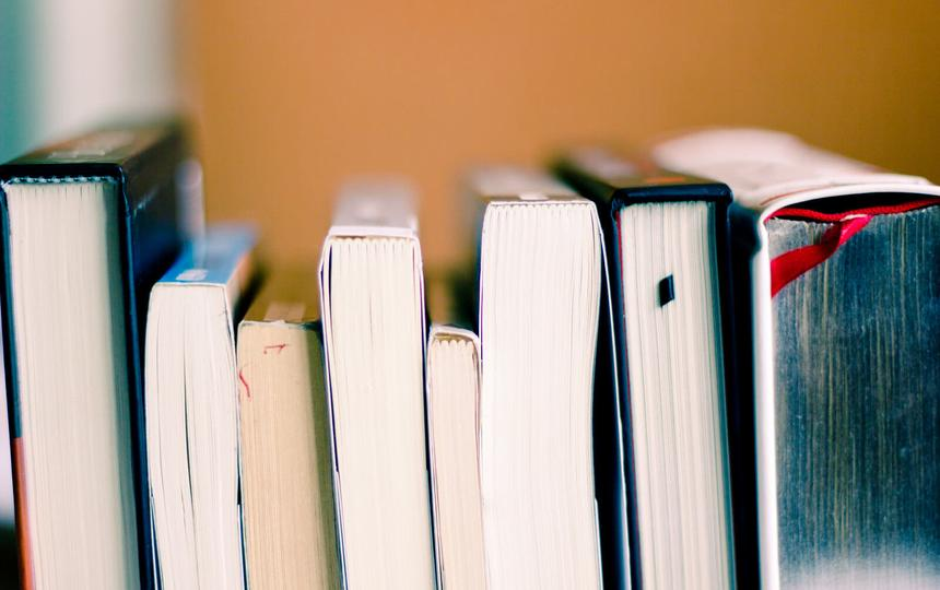 livros deitados, de forma que é possível ver apenas as parte de baixo das páginas