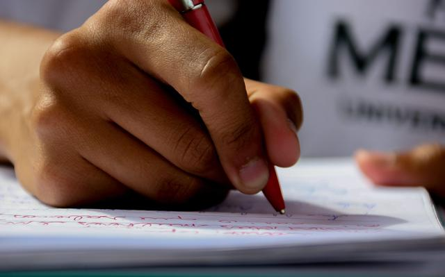 foco em mão de aluno escrevendo em caderno com caneta de corpo vermelho