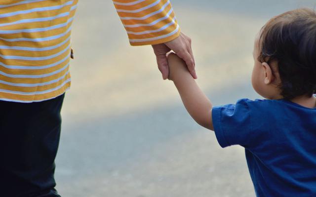 adulto de camiseta listrada segura a mão de criança pequena