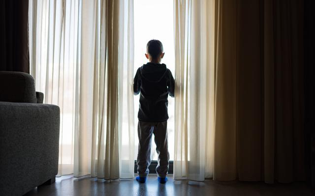 Menino em pé, de costas para a câmera. Ele olha através de uma grande janela, em meio às cortinas.