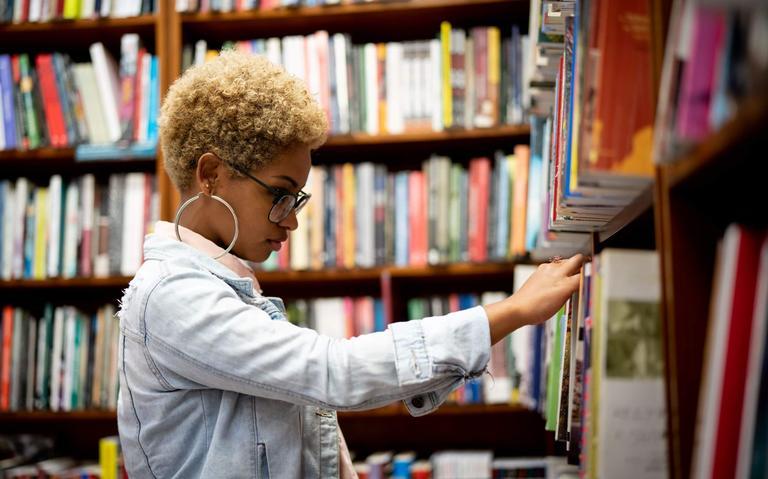 mulher negra vestindo jaqueta jeans, óculos e brincos de argola escolhe livro em prateleira de biblioteca