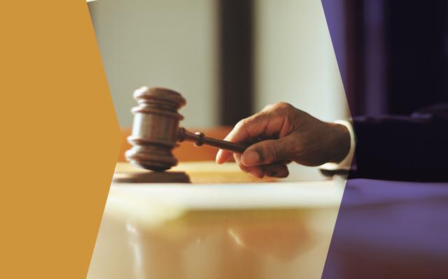 Mão segura um malhete (tipo de martelo usado por juízes) e parece batê-lo na mesa. A foto tem filtros nas cores roxa e laranja.