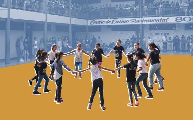 em primeiro plano, roda de crianças sorrindo de mãos dadas. em segundo plano, com filtro azul e amarelo, espectadores da apresentação observam as crianças em mezanino e no andar onde ocorre a apresentação.