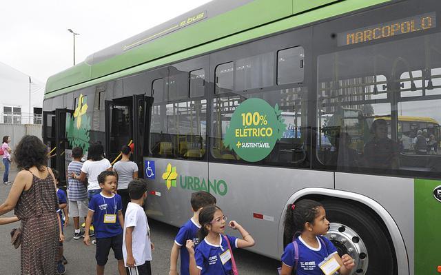 """crianças passam em frente a ônibus com adesivo onde se lê """"100% elétrico + sustentável"""""""