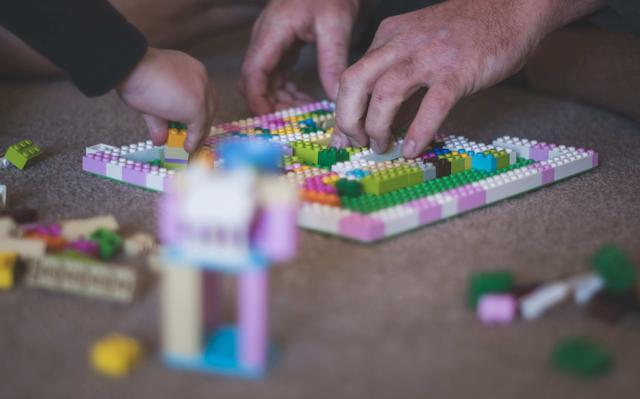 Em close, aparecem duas mãos, a de um adulto e a de uma criança. Eles montam blocos de Lego coloridos.