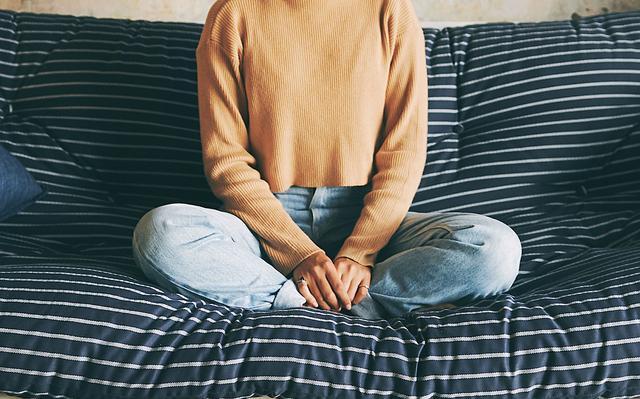 mulher sentada de pernas cruzadas em sofá com mãos sobre o colo