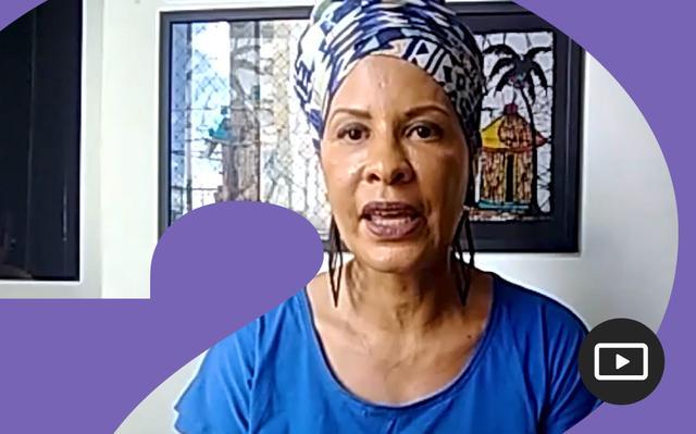 Anna Benite em entrevista feita em vídeo. Em volta da foto, há uma moldura roxa.