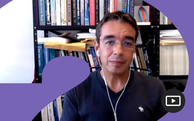 captura de vídeo onde o pesquisador juliano assunção, vestindo camiseta escura e óculos, está a frente de uma estante de livros