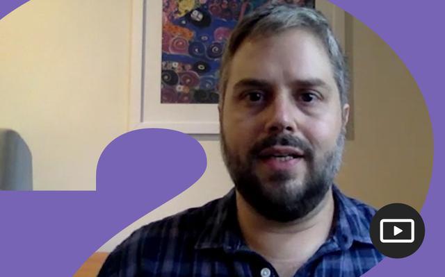 Luiz Guilherme Paiva em entrevista feita em vídeo. Em volta da foto, há uma moldura roxa.