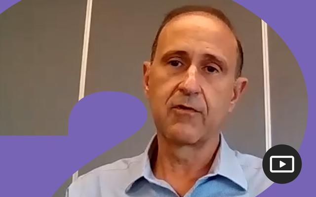 Marcelo Calliari em entrevista feita em vídeo. Em volta da foto, há uma moldura roxa.