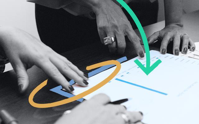 imagem em preto e branco de mãos apontando para papel com gráficos