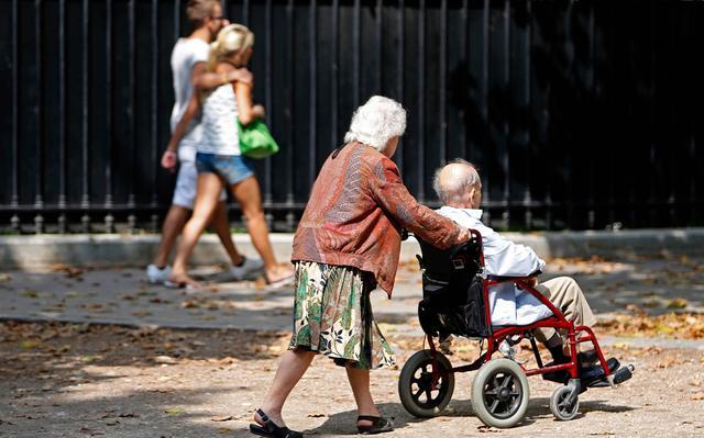 Casal de idosos passeia em parque. A mulher, de cabelos curtos, blusa vermelha e saia verde, guia o homem numa cadeira de rodas vermelha. Ao fundo, vê-se um casal de jovens, que andam abraçados. Uma luz de sol forte bate sobre a cena.