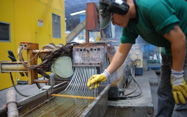 De perfil, um homem que usa boné verde e luvas amarelas se abaixa para manusear diversas tiras de plástico reciclado que saem de uma máquina. Ele está em um ambiente fabril, com grande maquinário e paredes amarelas.