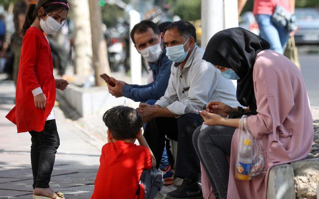 cinco pessoas esperam e conversam sentadas na calçada. dois homens, uma mulher adulta e duas crianças: uma menina que fica em pé de frente para a família e um menino agachado na frente da mulher.