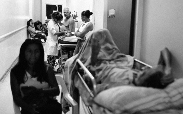 Imagem em preto e branco de pacientes em macas, acompanhantes e pessoas em espera, todas em corredor apertado. Um dos pacientes está sentado na maca enquanto profissional de saúde o examina.