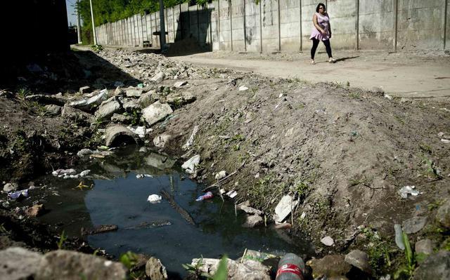 Uma mulher caminha por uma rua. Ao lado, há um córrego sujo, um esgoto a céu aberto, também poluído com lixo.