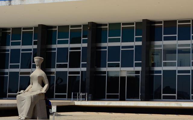 A fachada do edifício do Supremo Tribunal Federal. À frente, há uma estátua de uma mulher sentada e de olhos vendados, segurando uma espada sobre seu colo, que representa a Justiça. O prédio tem diversas janelas de vidro e estrutura de concreto aparente.