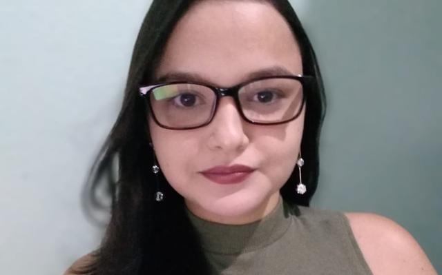 Selfie de mulher que veste blusa verde sem mangas com gola alta, e óculos. Ela tem cabelos escuros, lisos e compridos