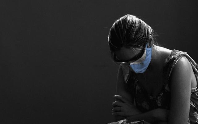 mulher de máscara olha para baixo