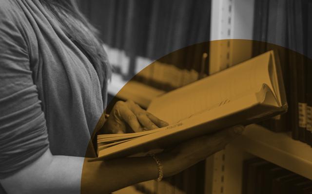 imagem aproximada em preto e branco de pessoa abrindo livro próximo a estante de biblioteca