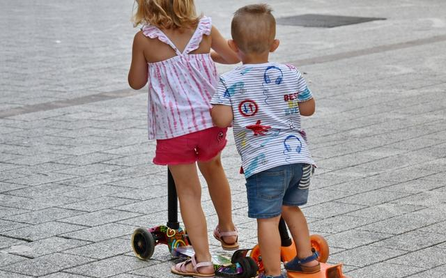 menino e menina de costas andando de patinete