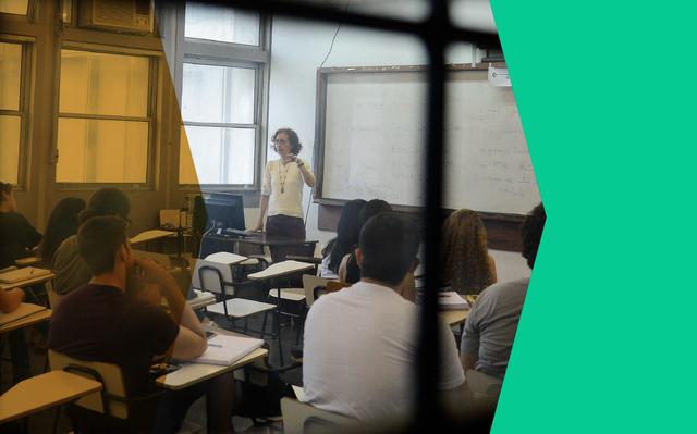 Sala de aula em universidade. Professora está em frente à lousa falando com alunos sentados em carteiras.