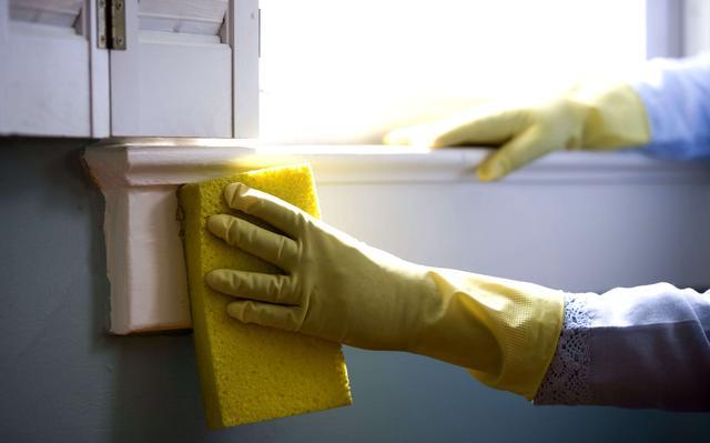mãos enluvadas passam bucha amarela em parapeito de janela