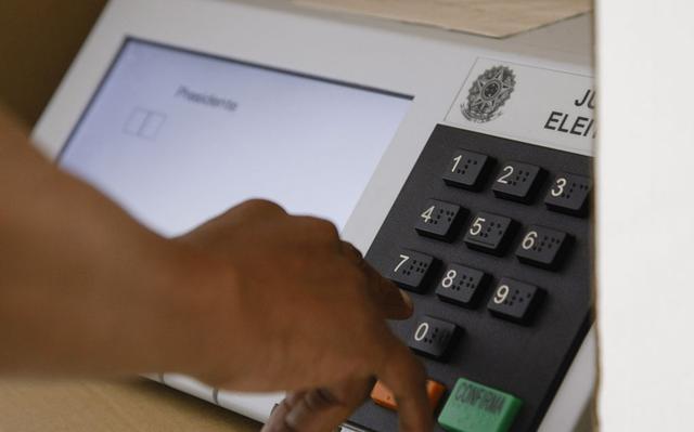 mão prestes a apertar botões em urna eletrônica